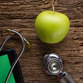 Alternative medicine - stethoscope, clipboard and green apple on wood table top view . Medical background. Concept for diet, healthcare, nutrition or medical insurance — Stock Photo