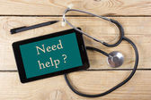 Need help ? - Workplace of a doctor. Tablet, medical stethoscope, black pen on wooden desk background. Top view — Stock Photo