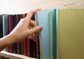 Women Hand selecting book from a bookshelf in library. Back to school. — Stock Photo