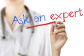 "Female doctor with stethoscope writing ""Ask an expert !"" . Hand holding pen isolated on white. Medical background. — Stock Photo"