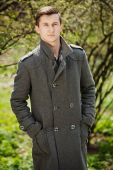 Young man in a gray coat — Stock Photo