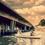 Two men in a canoe by a bridge — Stock Photo #52132107
