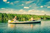 Young men rowing in a canoe — Stock Photo