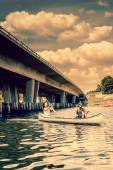 Two men in a canoe by a bridge — Stock Photo