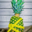 Pineapple with measure tape on a table — Stock Photo #76584045