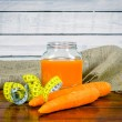Carrot juice with measure tape on a table — Stock Photo #76584087