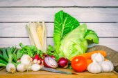 Vegetables on a wooden table with a knife — Stockfoto