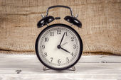 Classic alarm clock on a wooden table — Stock Photo