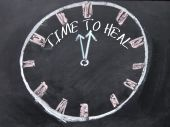 Time to heal text and hourglass sign on blackboard — Stock Photo