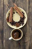 Cup of coffee with cinnamon sticks on wood — Stock Photo