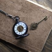 Antique book and pocket watch on grunge wooden table — Stock Photo