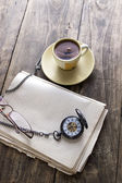 Vintage pocket watch with cup of coffee on old book — Stock Photo