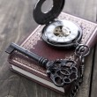 Pocket watch and old key on wooden table — Stock Photo #62689397