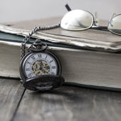 An antique pocket watch, glasses and bible  — Stockfoto