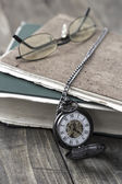 An antique pocket watch, glasses and books — Stockfoto
