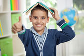 Funny schoolboy with a book on head — Stock Photo