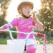 Portrait of girl in a pink safety helmet on her bike blowing a d — Stock Photo #53075105