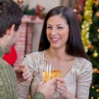 Couple holding glasses with champagne and celebrate Christmas ni — Stock Photo #53075775