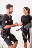 Female coach giving man ems electro muscular stimulation exercis — Stock Photo