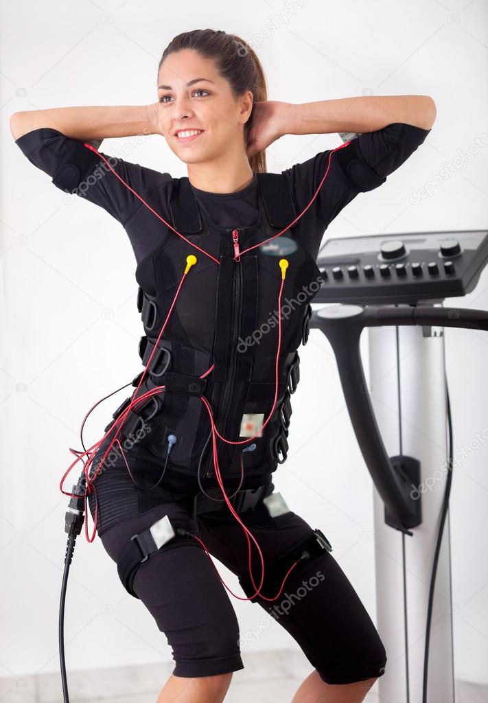 Woman exercise trunk-bending forward on electro stimulation ma - Stock ...
