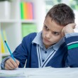 Angry and tired schoolboy studying — Stock Photo #54056893