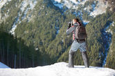 Photographer photographing winter panorama in  mountains — Stock Photo