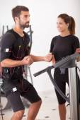 Female coach giving man ems electro muscular stimulation exerci — Stock Photo