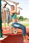 Jovem mulher exercitando com equipamentos de ginástica em público par — Foto Stock