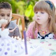 Kids celebrating birthday party and blowing candles on cake  — Stock Photo #55172369