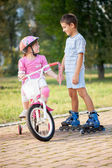 Brother and sister outdoors riding bikes and roller  — Stockfoto