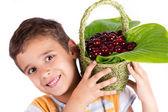 Young happy boy holding cherry basket — Stockfoto