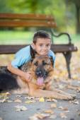 Child with a German Shepherd Dog in the park — Stock Photo