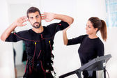 Female coach giving man ems electro muscular stimulation exerci — Stock Photo