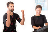 Female coach giving man ems electro muscular stimulation exercis — Stock Photo