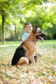 Smiling child with a German Shepherd Dog in the park — Foto Stock