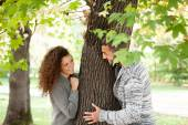 couple  in autumnal woods, peeking from behind a tree — Photo