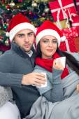 Young and smiling couple with santa hat relaxing in X- mas night — Stok fotoğraf