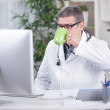 Senior doctor in the office working on the computer an drink cof — Stock Photo #59188397