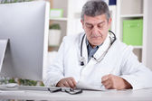 Physician with stethoscope around his neck working in office — Stock Photo