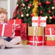 Pretty little girl smiling with present near the Christmas tree — Stock Photo #60153663