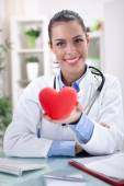 Friendly young female doctor holding a heart in his hands — Stock Photo