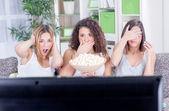 Three beautiful young girls  watching sad movie depressed — Stock Photo