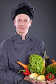 chef holding a basket of delicious fresh vegetables — Stock Photo