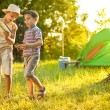 Children on a camping trip learning how to read and use a map — Stock Photo #63589587