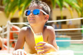 Young boy with sunglasses on beach enjoys and holding juice — Stock Photo