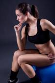Young fit woman on black background — Stock Photo