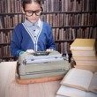 Little boy writer on desk with typewriter in library — Stock Photo #70406239