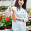 Young smiling woman florist working in the greenhouse — Stock Photo #73384329