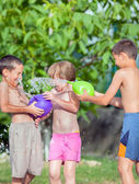Three happy children play and splashes with water in a park or h — Stock Photo