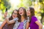 Happy teen girls taking selfie in park — Photo